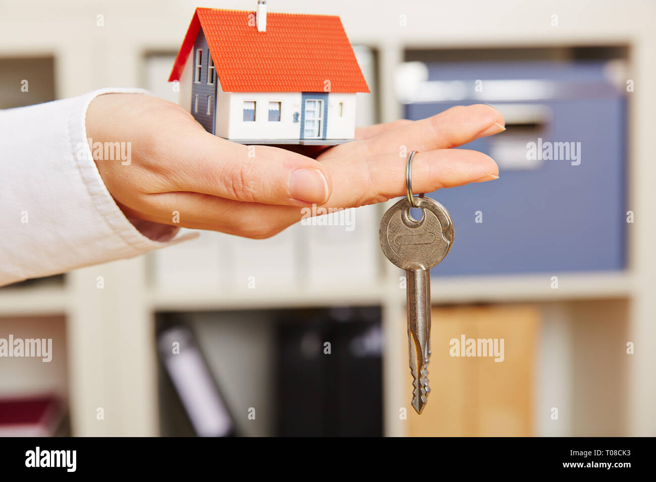 Hand of a woman holds a small house with key Stock Photo