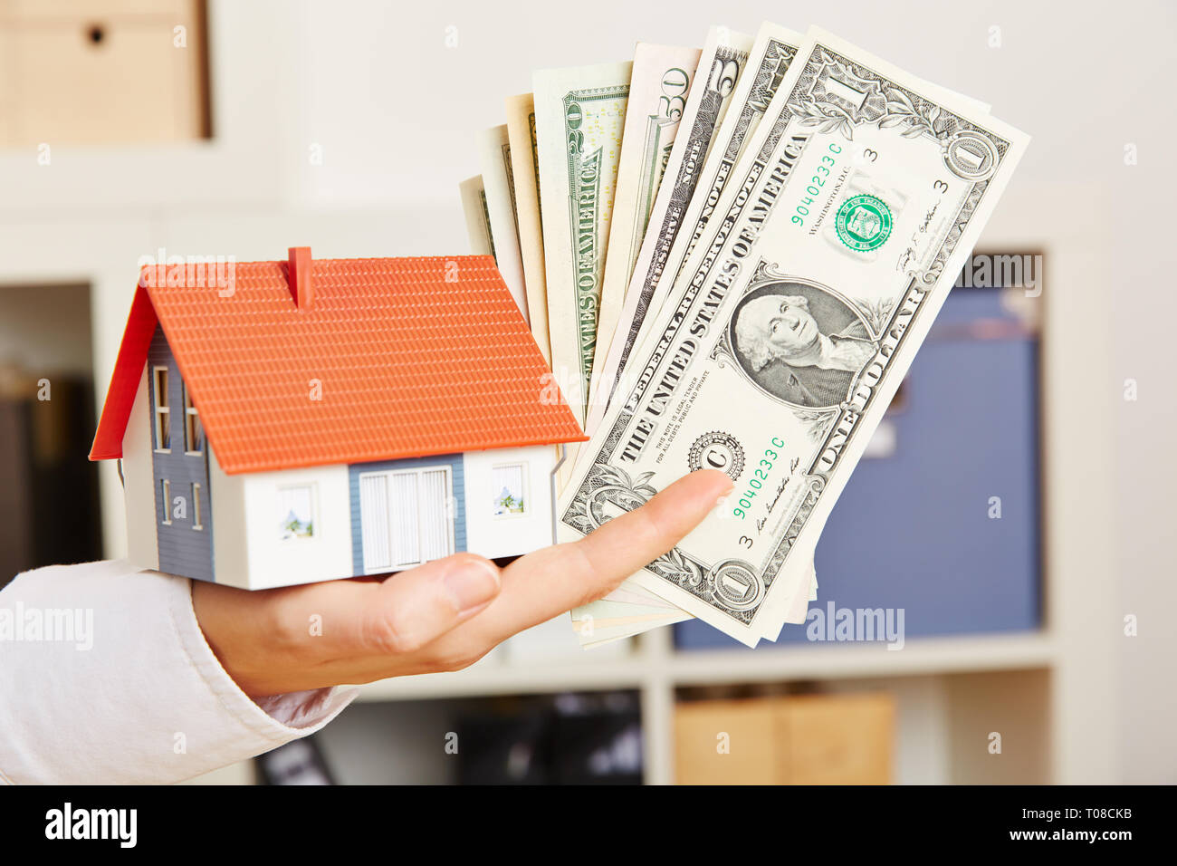 Female hand holds dollars and a small house as a symbol for mortgage lending Stock Photo