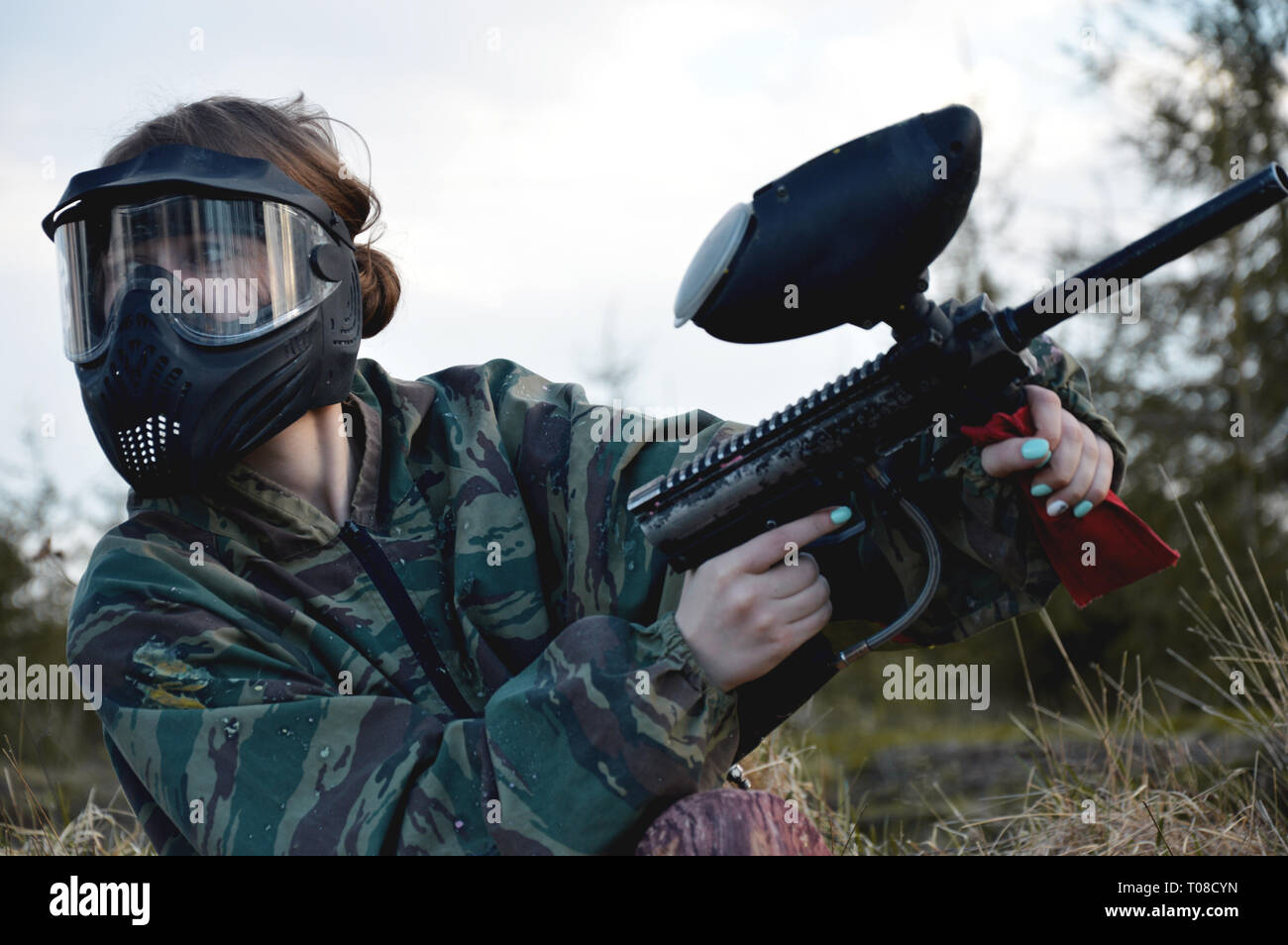 Paintball sport player girl in protective camouflage uniform and mask with marker gun outdoors - Stock Image