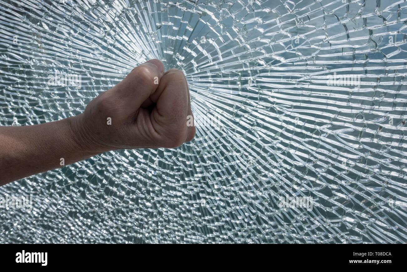 Fist on shattered window. Concept image, rage, anger, frustration, vandalism... - Stock Image