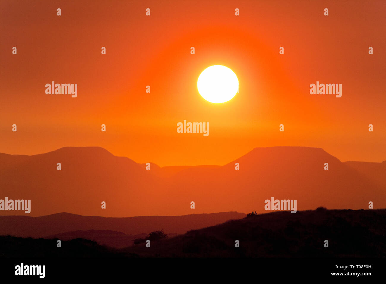 Africa, Namibia, Damaraland.  Dramatic sunset caused by atmospheric dust in dry mountain scenery. - Stock Image