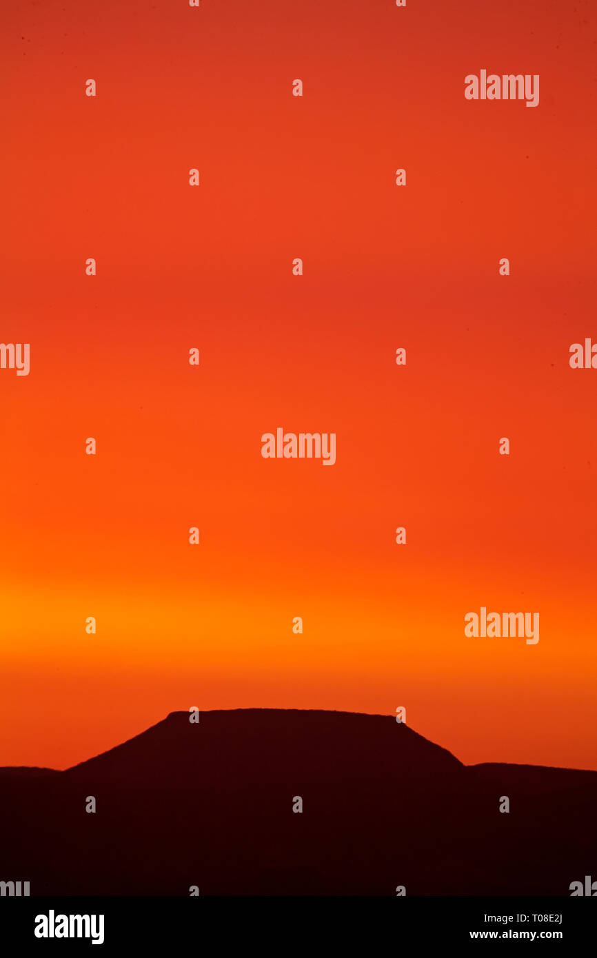 Africa, Namibia, Damaraland. Table Mountain under blood red sunset caused by dust in the sky. - Stock Image