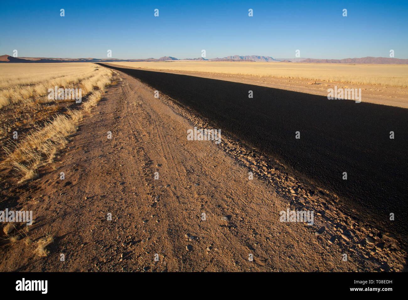 Africa, Namibia, Namib Desert. Road across empty desert plain. - Stock Image