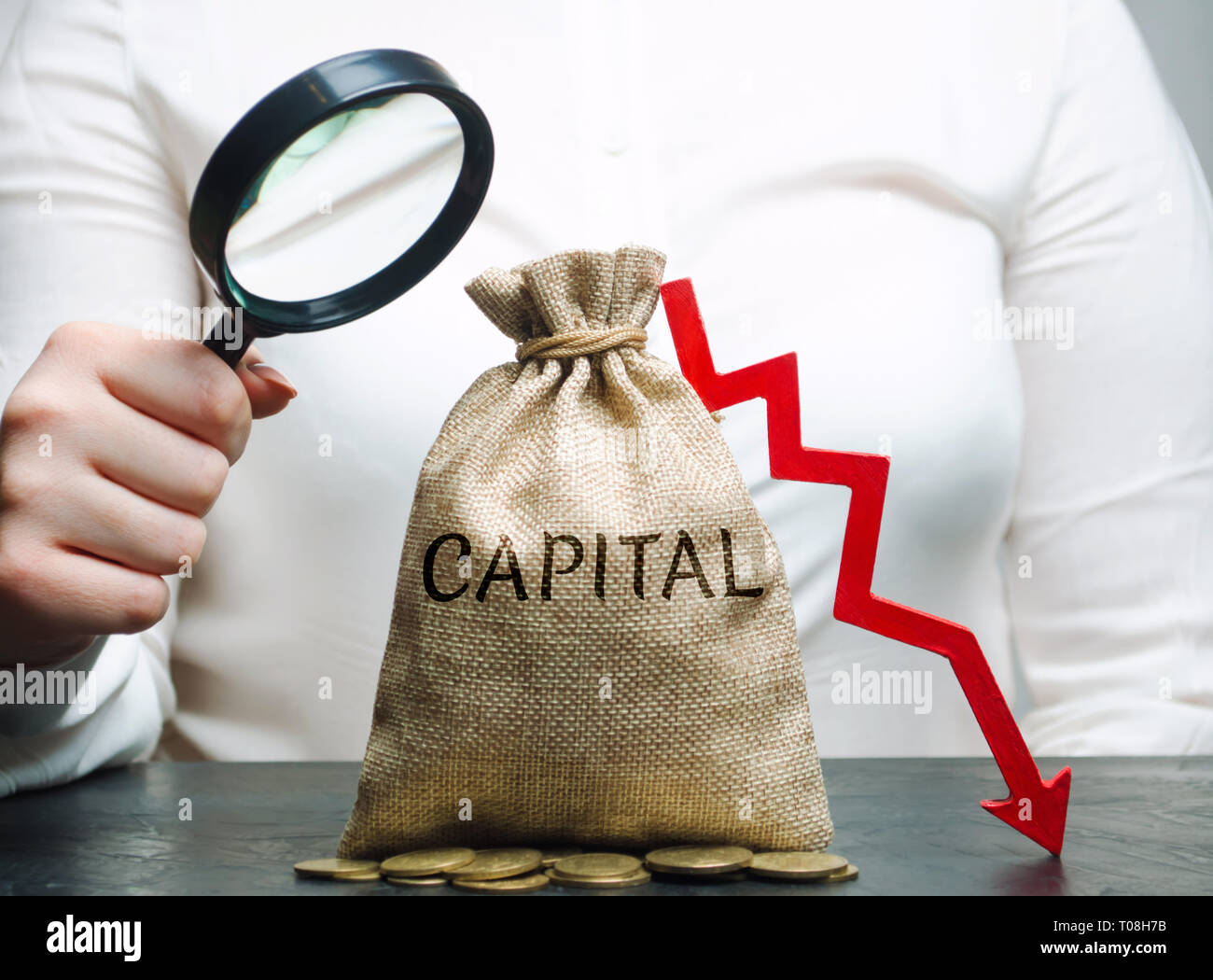 Woman analyzes data on the cost of capital in the company. Capital outflow. Unprofitable activity of the enterprise. Low capital ratio. Small income a - Stock Image