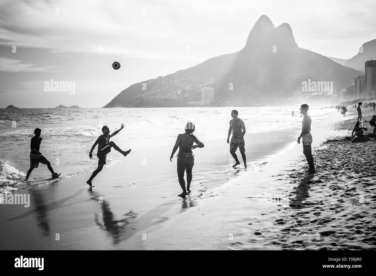 RIO DE JANEIRO, BRAZIL - FEBRUARY 24, 2015: A group of Brazilians playing on the shore of Ipanema Beach, with the famous Dois Irmaos mountain behind them Stock Photo