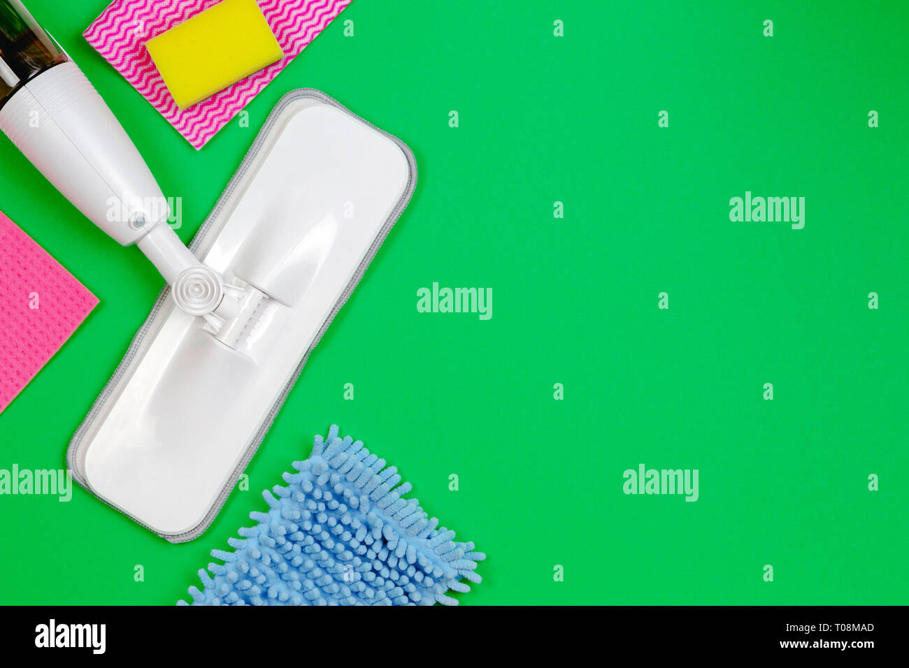 Housework, housekeeping, household, cleaning service concept. Cleaning spray mop with rags and sponges on green background - Stock Image
