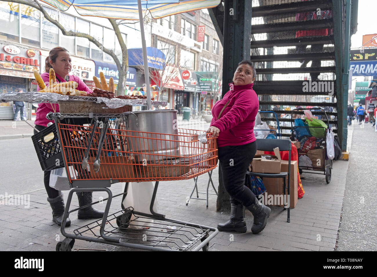 On a cold winter day, two women selling freshly grilled corn & grilled meat. On 82nd St. in Jackson Heights, Queens, NYC under the #7 train stairway. - Stock Image