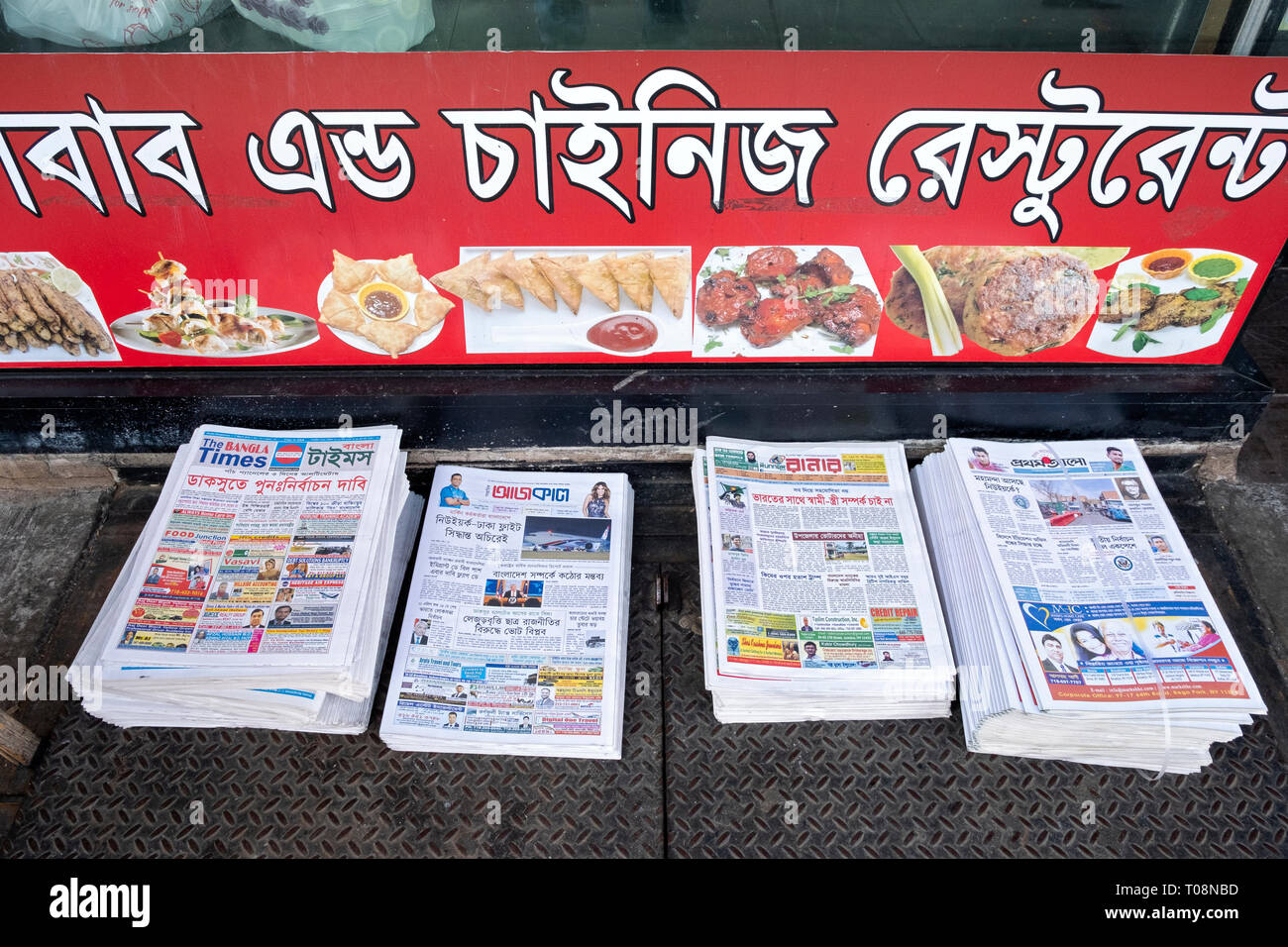 Piles of free Begali newspapers piled up outside a Bangladesh restaurant on 74th Street in Jackson Heights, Queens, New York City - Stock Image