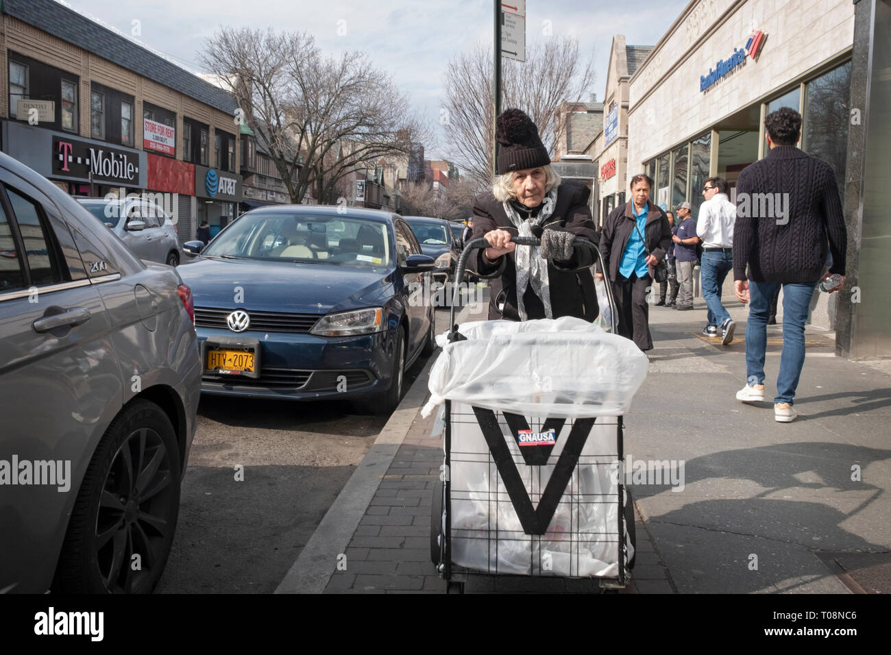 An older woman in a knit hat pushing a shopping cart on 82nd St. in Jackson Heights, Queens, NYC near the #7 train . - Stock Image