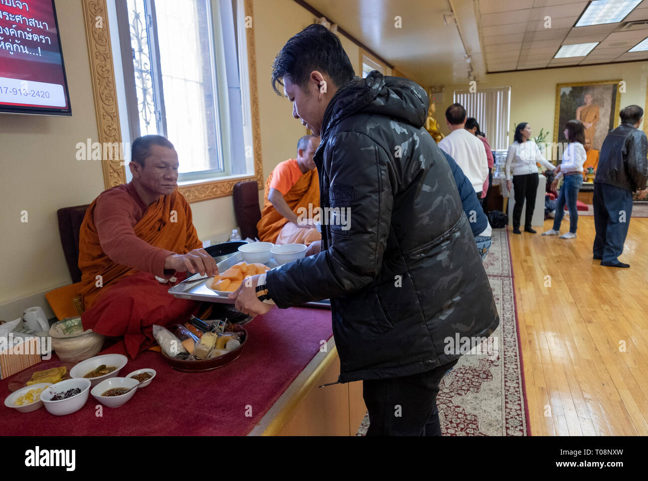 Worshippers at a Buddhist temple form an assembly line to serve food especially prepared for their monks. In Elmhurst, Queens, New York City. - Stock Image