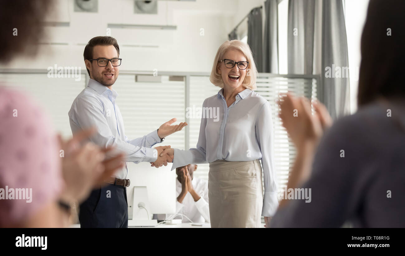 Happy manager boss praising old employee get team appreciation - Stock Image
