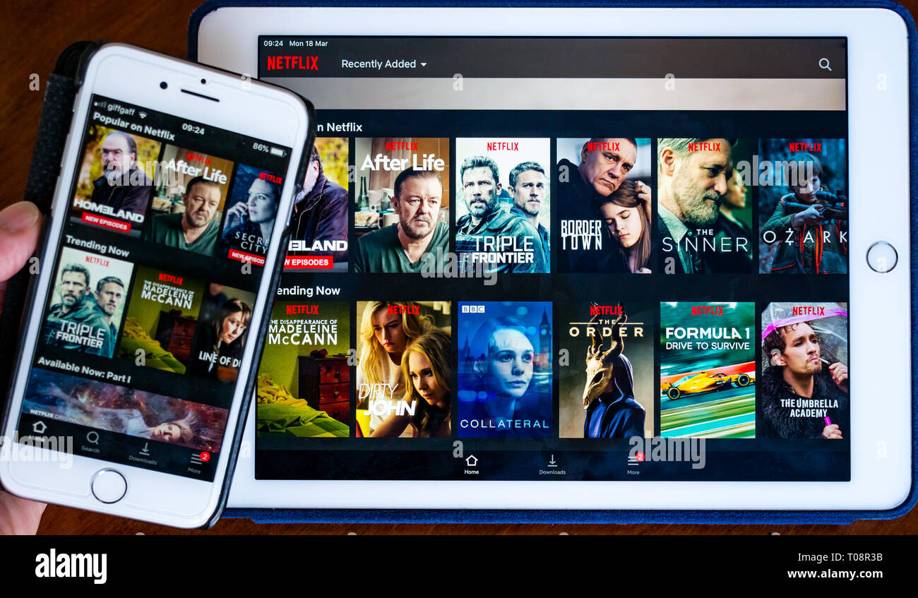 Apple iPhone 8 and Apple iPad Air showing Netflix app on screen with movie selection titles - Stock Image