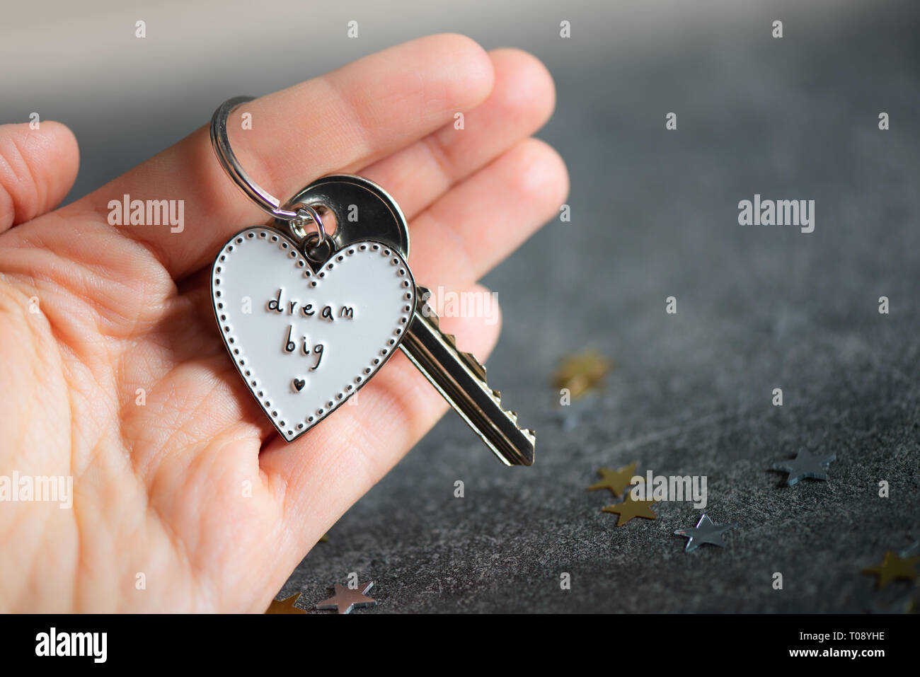 Keyring in the shape of heart and slogan DREAM BIG plus key from new home. Minimalist Concept of buying new home Stock Photo