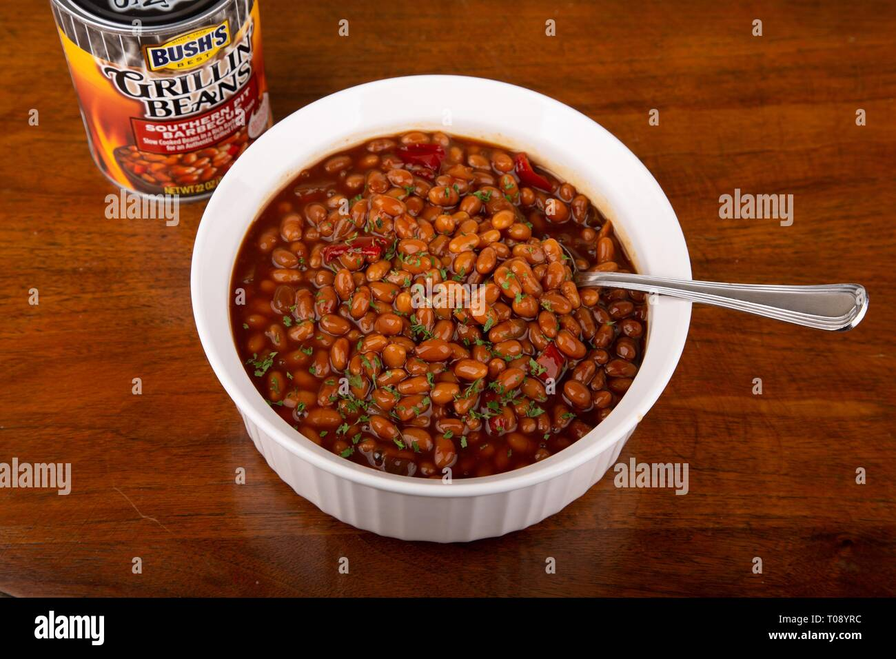 ATLANTA, GEORGIA - April 21, 2017: Bush's Grillin Beans in a can and white mug on a wood table. - Stock Image