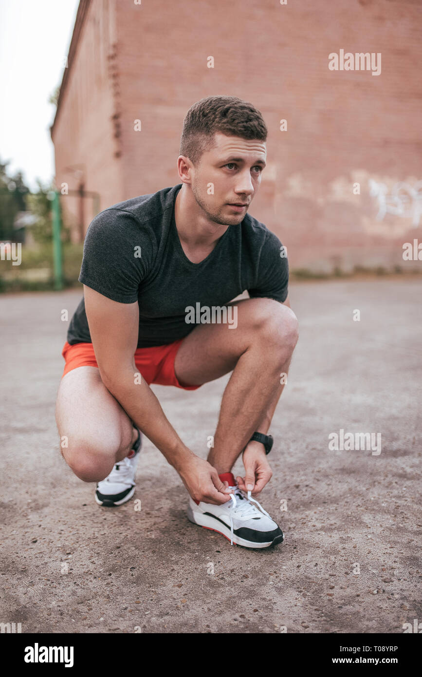 Athlete man crouched, tying shoelaces on sneakers. In the summer on the sports ground in the city. Trainer guy in the watch tracker bracelet after Stock Photo