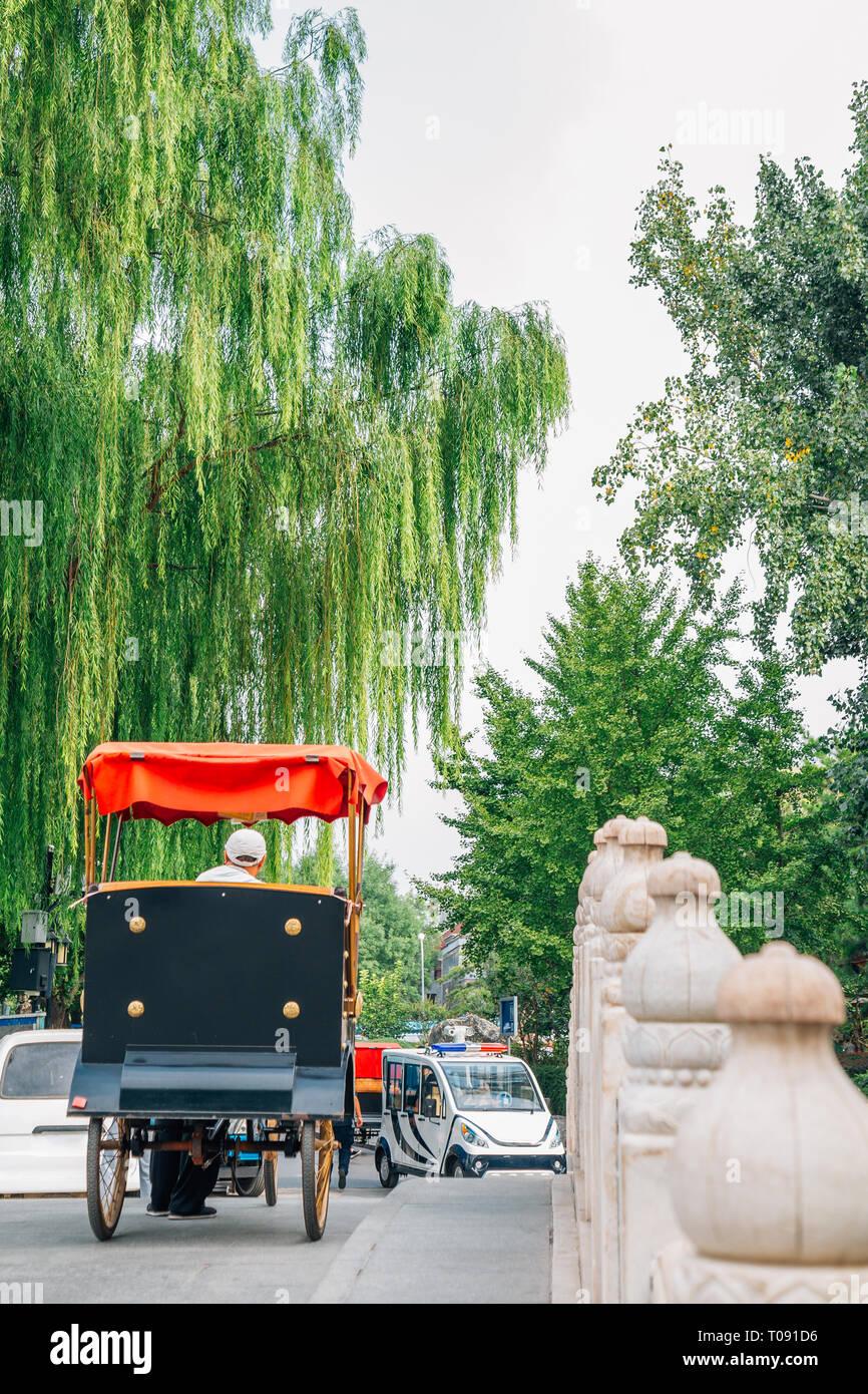 Chinese old traditional rickshaw on Jinding Bridge at Shichahai Qianhai lake in Beijing, China - Stock Image