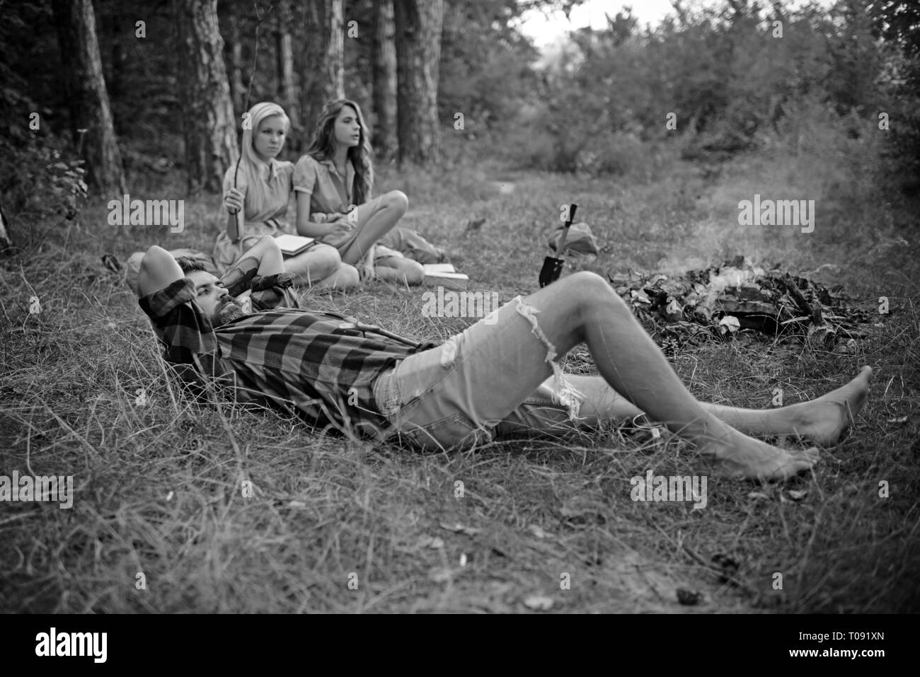 Bearded man in lumberjack shirt lying on grass and looking into the sky, unity with nature concept. Group of friends camping in forest - Stock Image