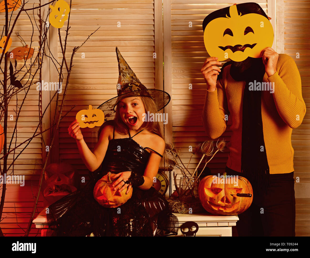 Small girl enjoy halloween party with father. Small girl and father celebrate halloween. Party time. Its the season for Halloween howls and pumpkin - Stock Image