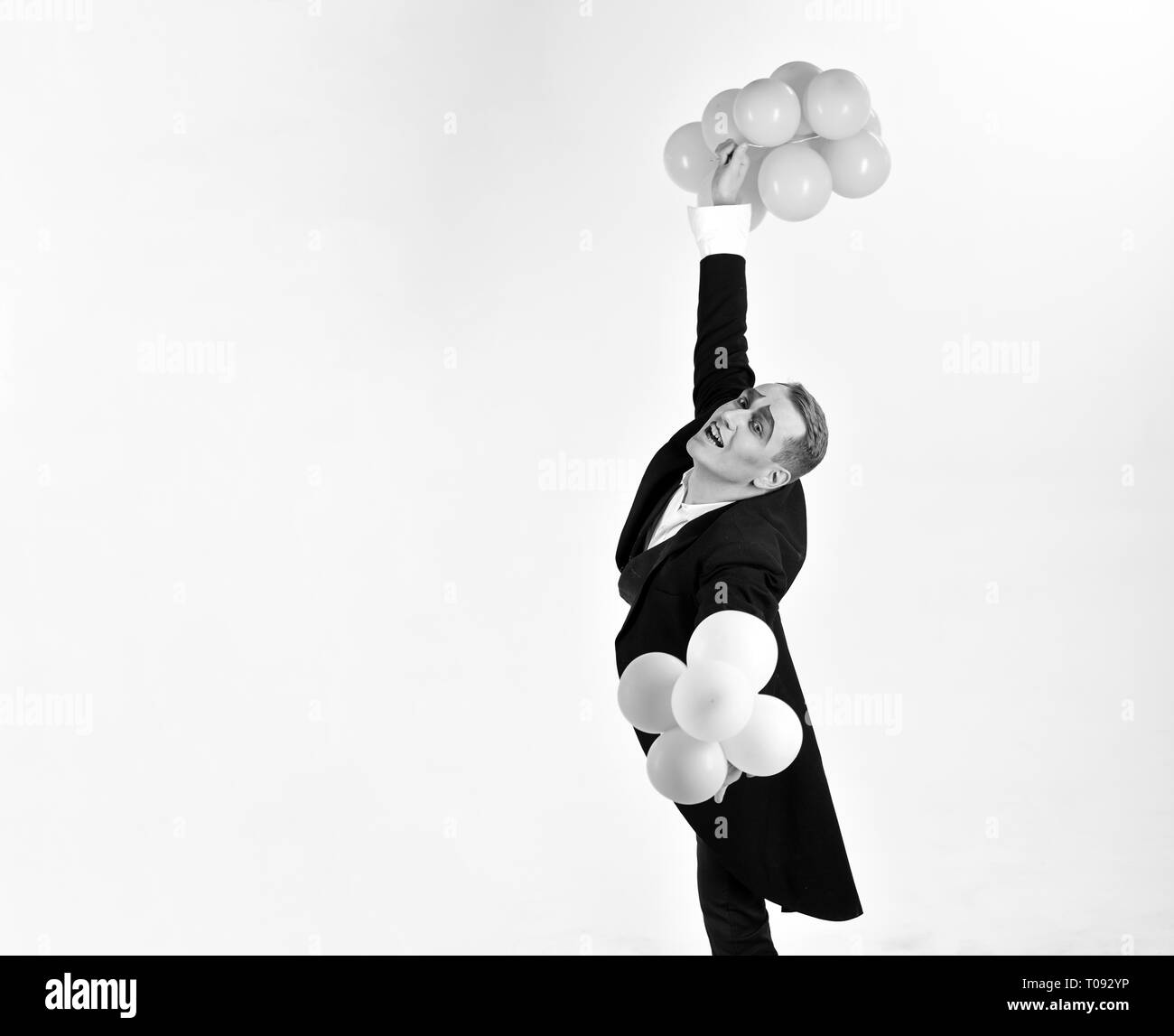 Happy birthday or anniversary celebration. Mime man with party balloons. Man with mime makeup on birthday party. Balloon artist. Holding festive - Stock Image