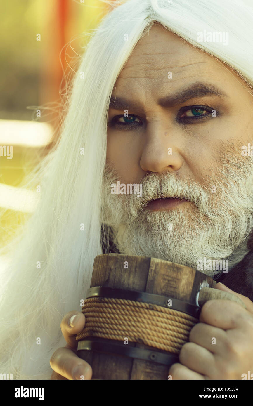 Old druid with wooden mug - Stock Image