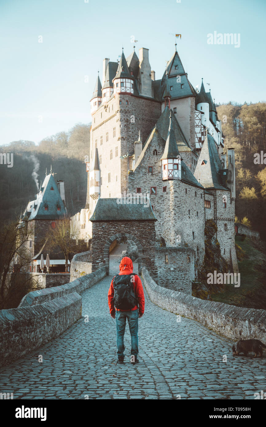 Panorama view of young explorer with backpack taking in the view at famous Eltz Castle at sunrise in fall, Rheinland-Pfalz, Germany - Stock Image