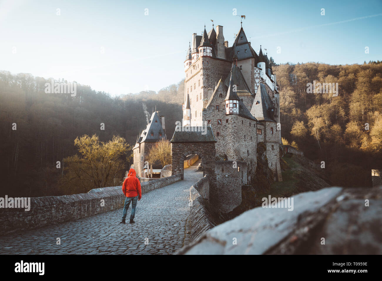 Panorama view of young explorer with backpack taking in the view at famous Eltz Castle at sunrise in fall, Rheinland-Pfalz, Germany Stock Photo