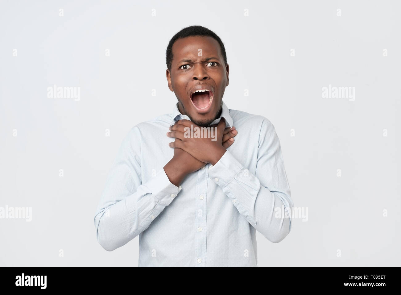 Young african man having asthma attack or choking can not breath suffering from respiration problems - Stock Image