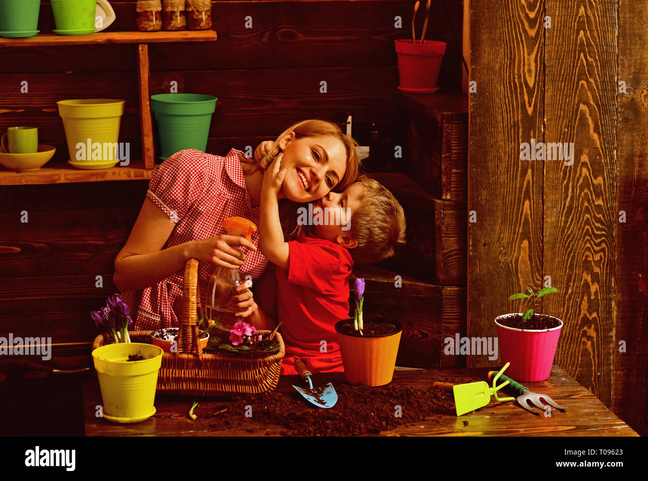 Love concept. Little child kiss mother planting flowers with love. Grown with love. Love and protect nature - Stock Image
