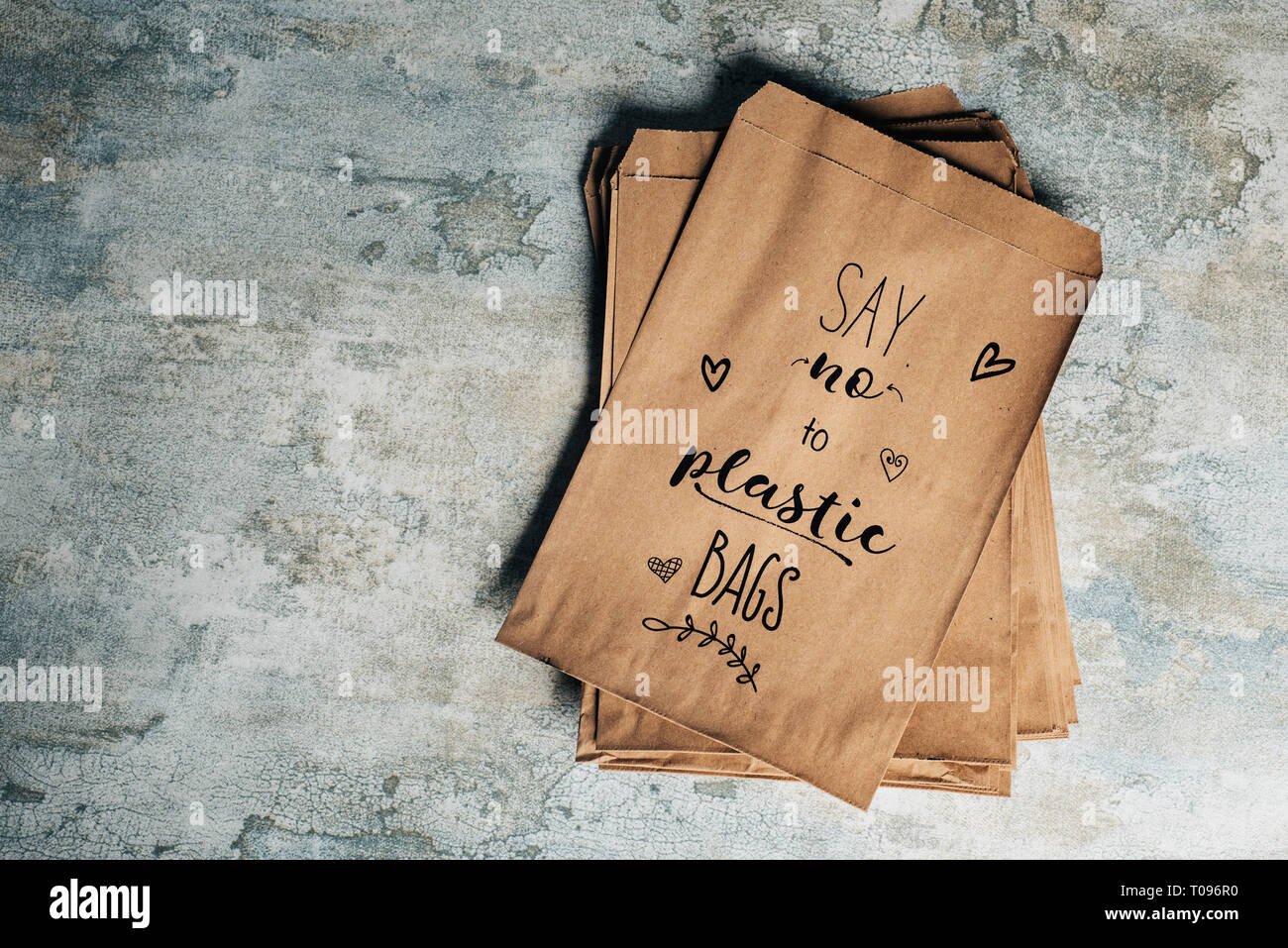 high angle view of some brown paper bags with the text say no to plastic bags written in the top one, on a stone surface - Stock Image