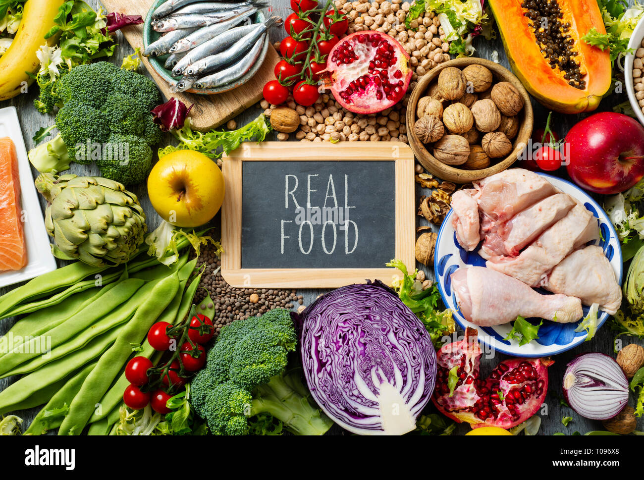 a chalkboard with the text real food written in it, on a pile of unprocessed food, such as different raw fruits and vegetables, some legumes and nuts, - Stock Image