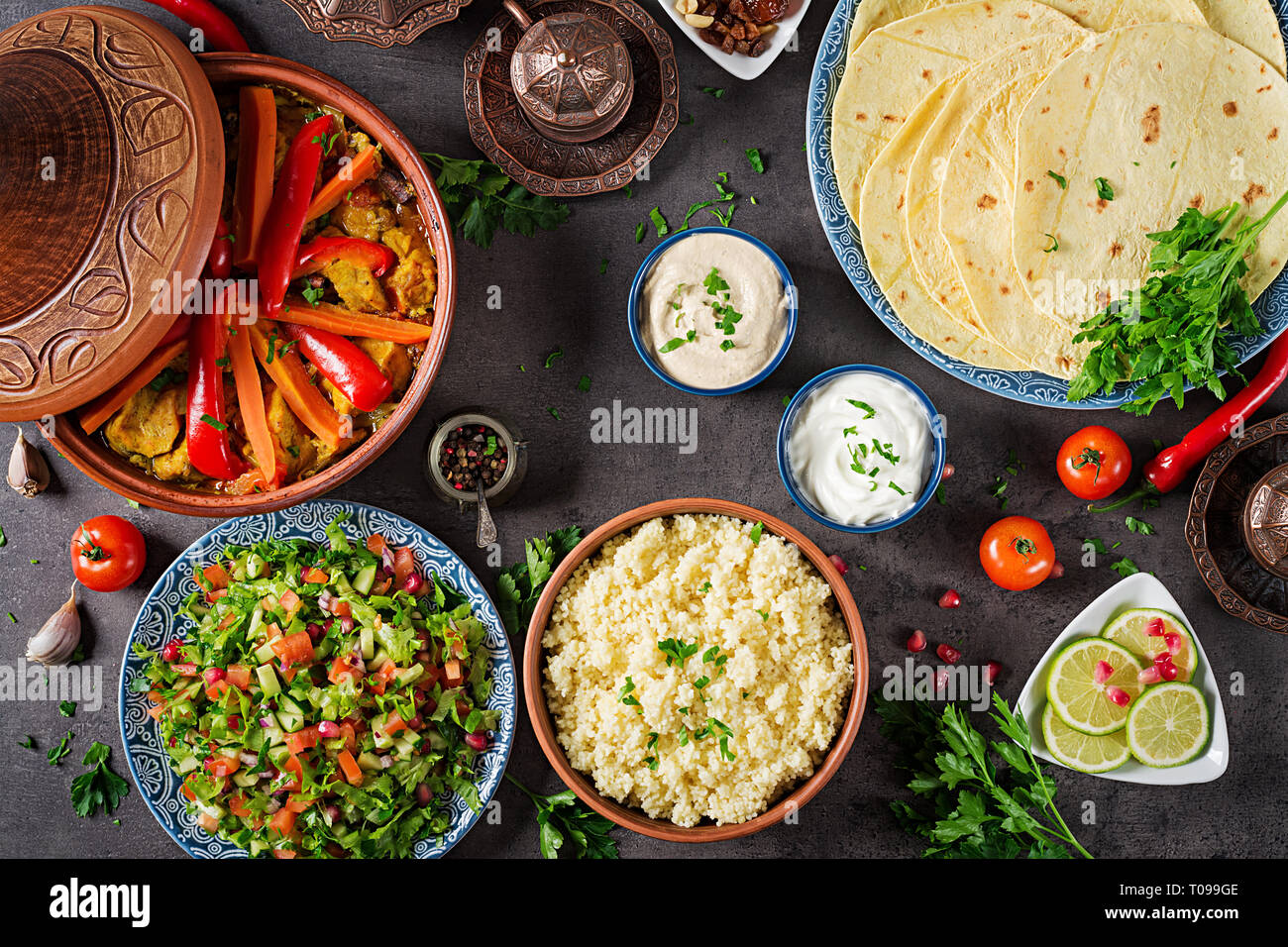 Moroccan food. Traditional tajine dishes, couscous  and fresh salad  on rustic wooden table. Tagine chicken meat and vegetables. Arabian cuisine. Top  Stock Photo