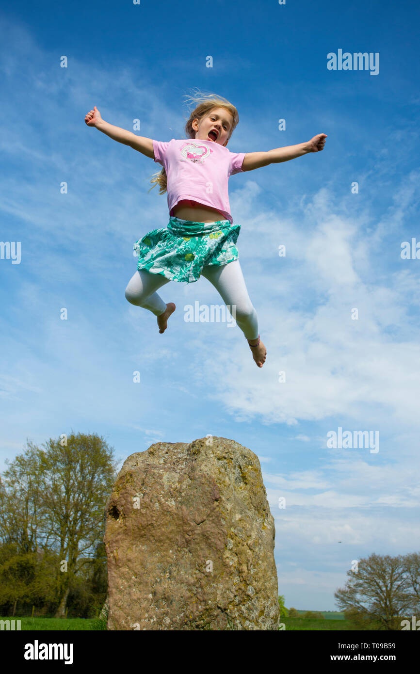 Great Britain, Wiltshire, Avebury Stone Circle.  Girl using power of levitation over an ancient stone megalith. MR. - Stock Image
