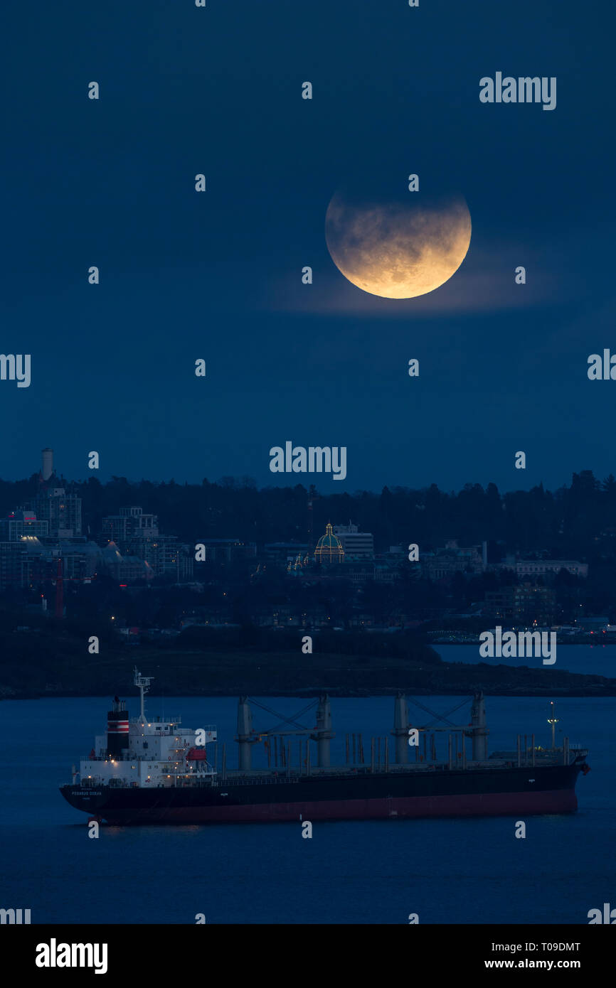 Blood moon rising over Victoria and freighter ship before phase of lunar eclipse-Victoria, British Columbia, Canada. - Stock Image