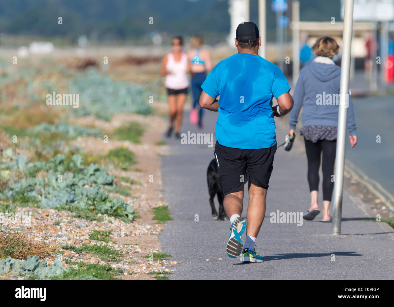 Man jogging by the roadside with sweat covering his shirt in Summer in the UK. Male jogger sweating, perspiring, back covered in perspiration. - Stock Image