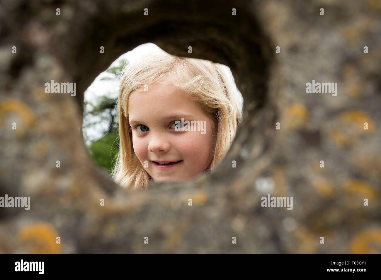 Great Britain, England, Oxfordshire, Rollright Stones.  Young girl looks through a natural hole in a megalith, possibly a pagan ritual dating back cen - Stock Image