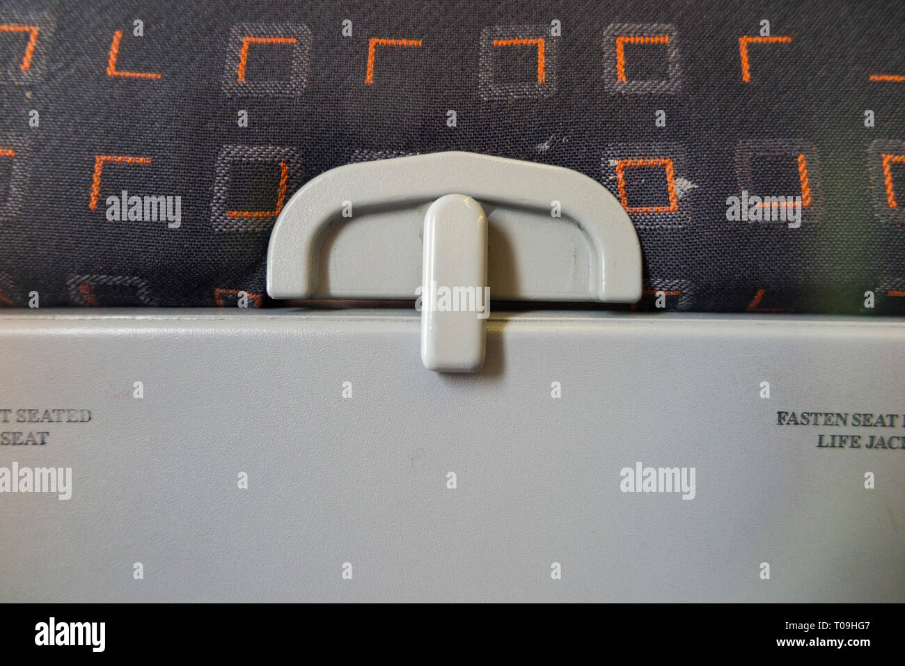 The latch / catch of a passenger 's seat tray table in folded up position ready for take off / landing on an Airbus A320 or A319 operated by Easyjet. (104) - Stock Image
