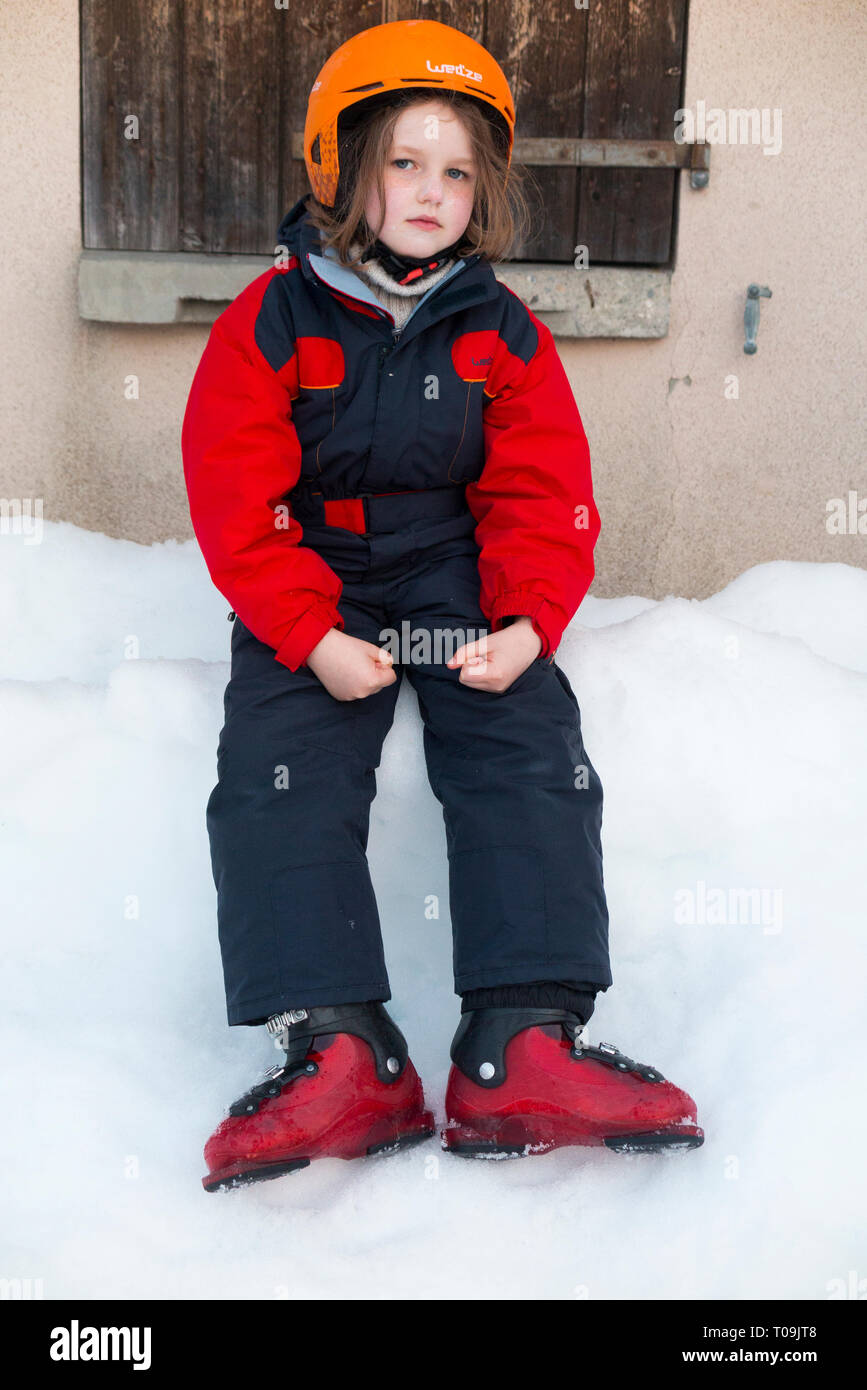 Six-year-old English girl on holiday and wearing ski suit and ski boots but without wearing skis and so not actually skiing. She looks tired, serious, & thoughtful. France (104) - Stock Image