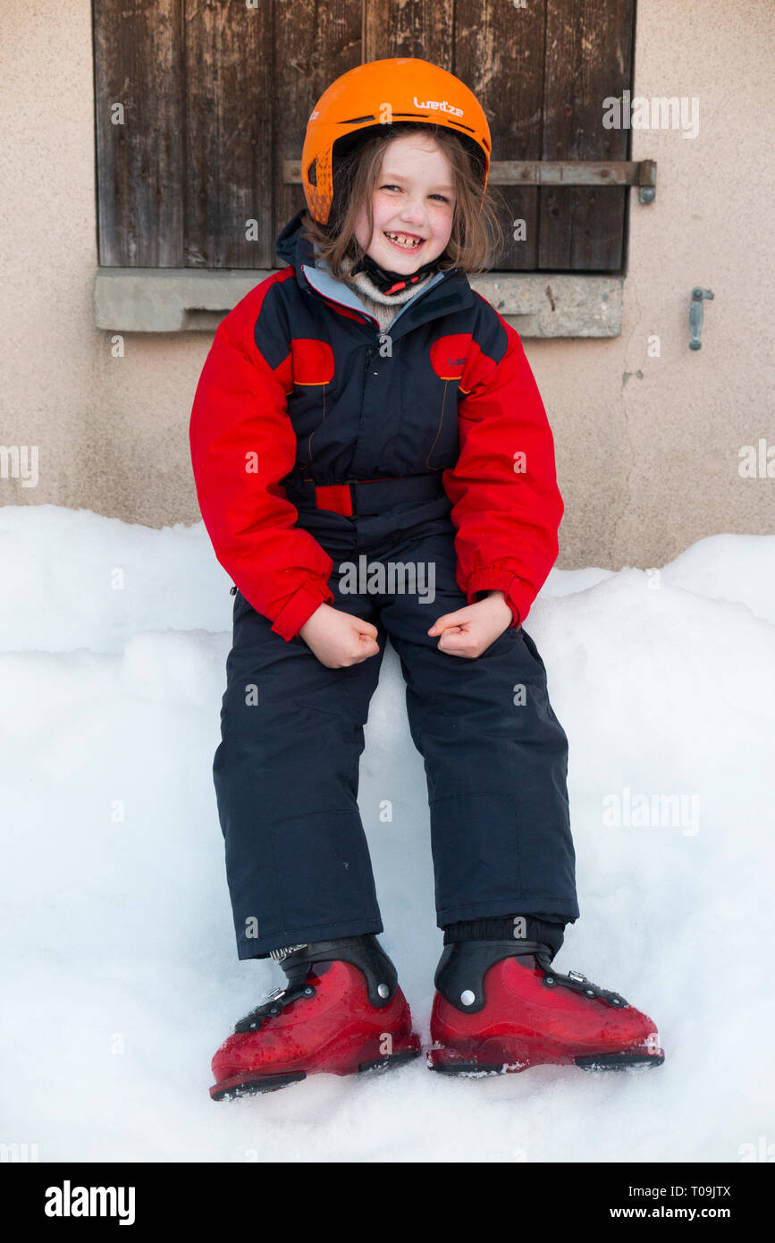 Six-year-old English girl on holiday and wearing ski suit and ski boots but without wearing skis and so not actually skiing. She looks happy. France (104) - Stock Image