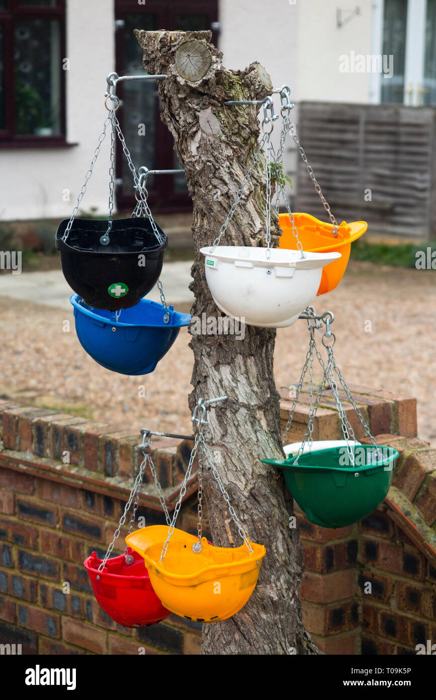 Several hanging baskets together, to decorate / use / disguise a dead tree stump; the hanging baskets are made of reused safety hardhat helmets. (104) - Stock Image