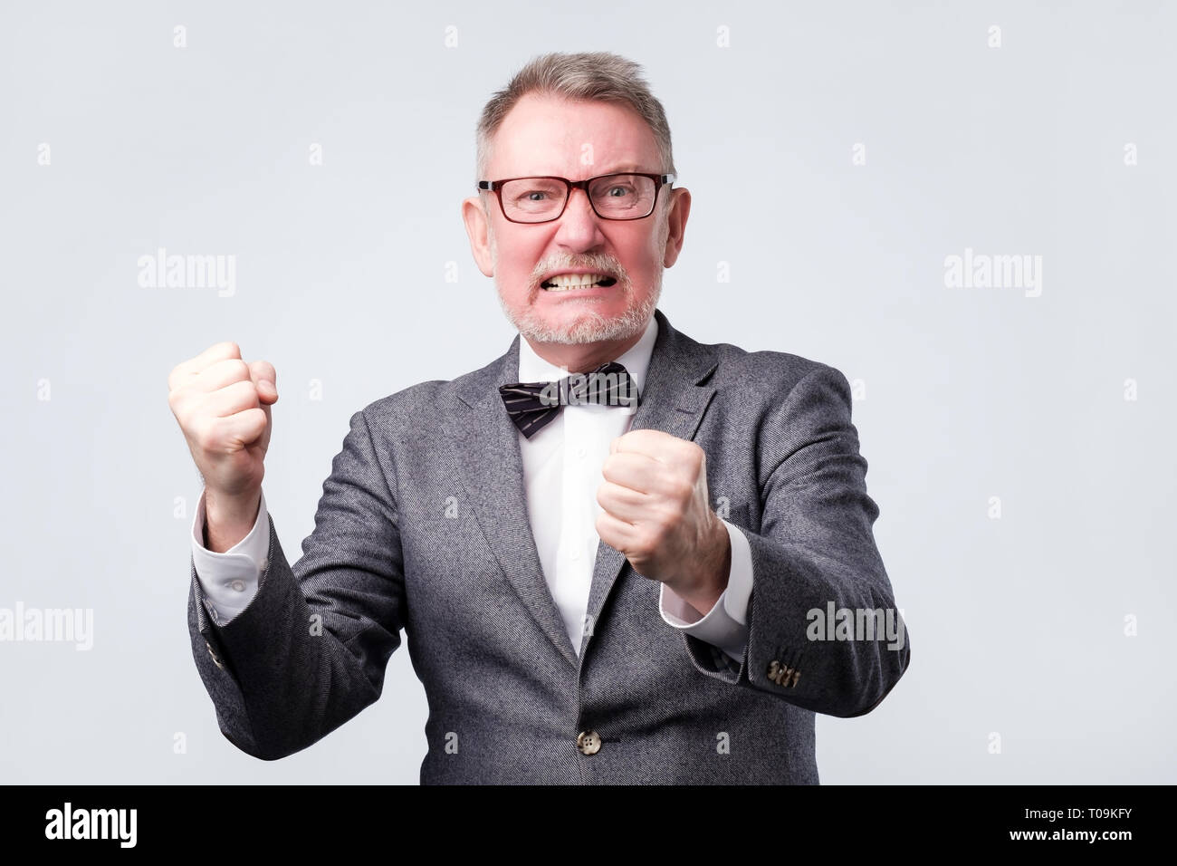 Handsome elegant senior man angry and mad raising fist up - Stock Image