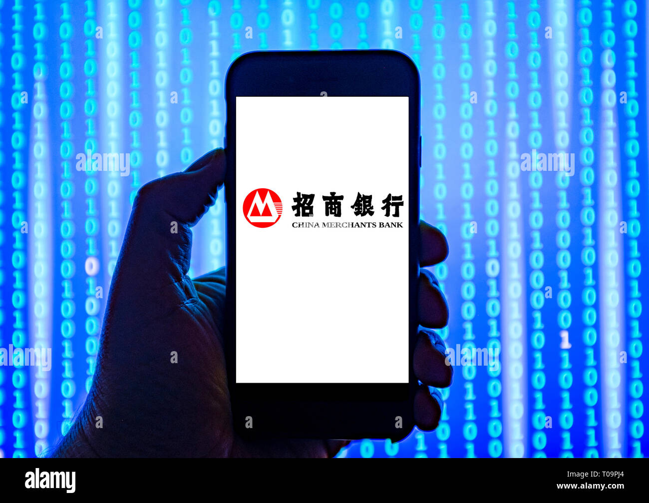 Person holding smart phone with China Merchants Bank  logo displayed on the screen. - Stock Image