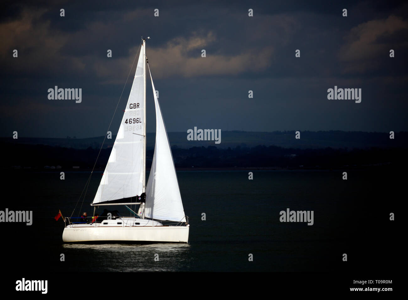 sailing,yacht,boat,in,bright,sunshine,with,dark,rain,storm,in,background,clouds,The Solent,Cowes,Isle of Wight,England, UK, Stock Photo