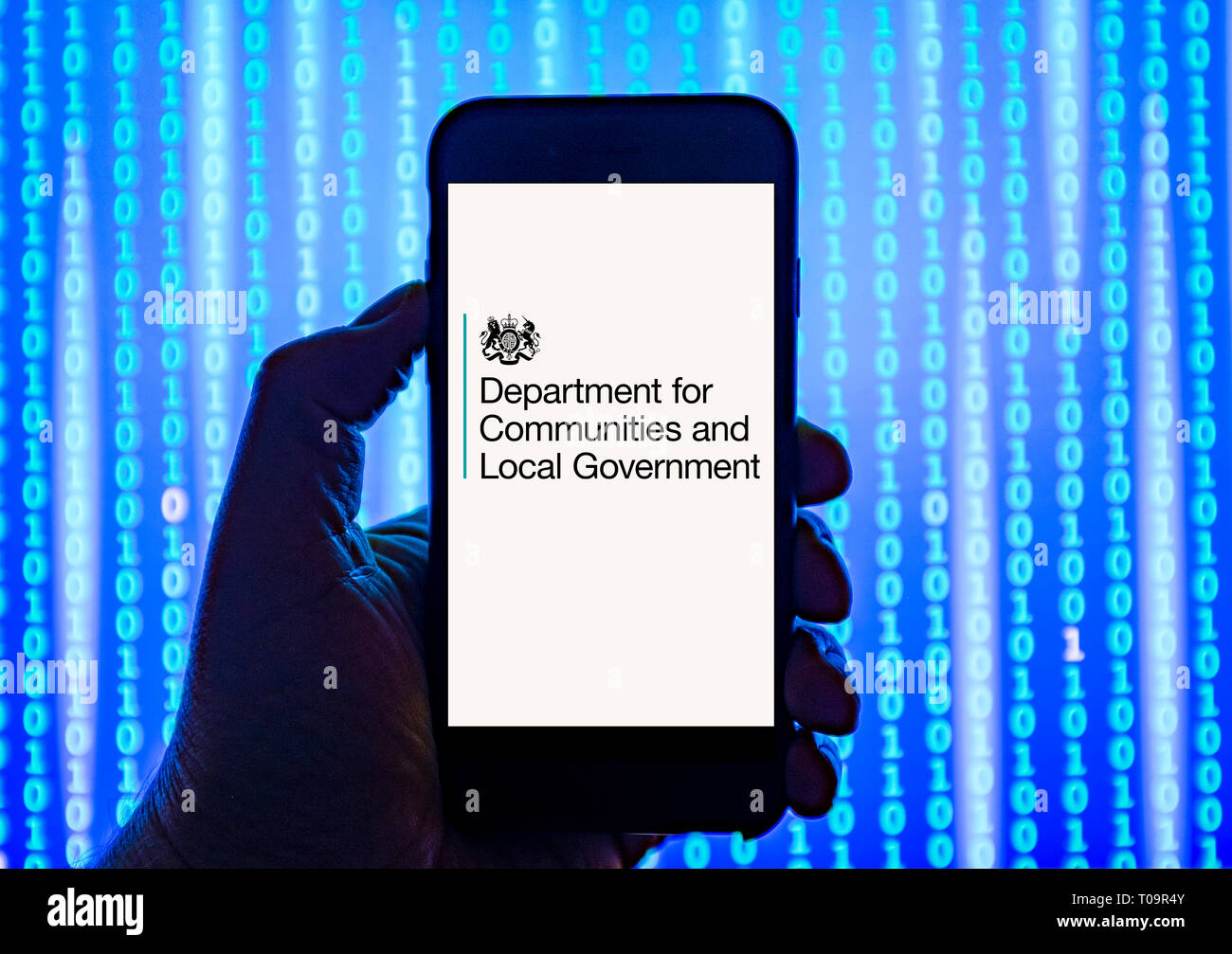 Person holding smart phone with Department for Communities and Local Government   logo displayed on the screen. - Stock Image