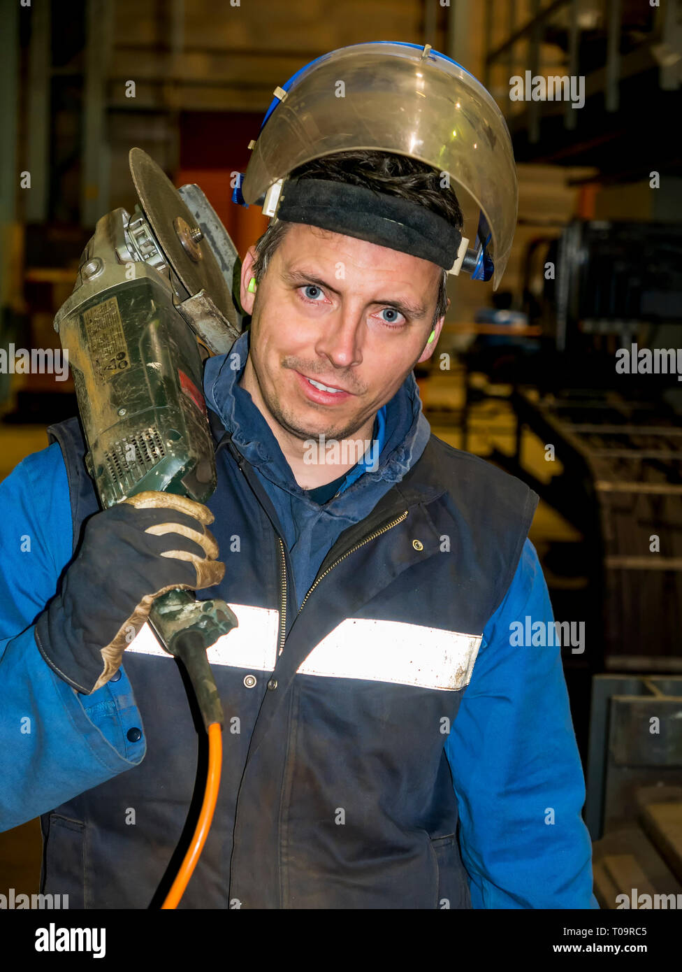 smiling construction worker, with  angle grinder over his shoulder - Stock Image