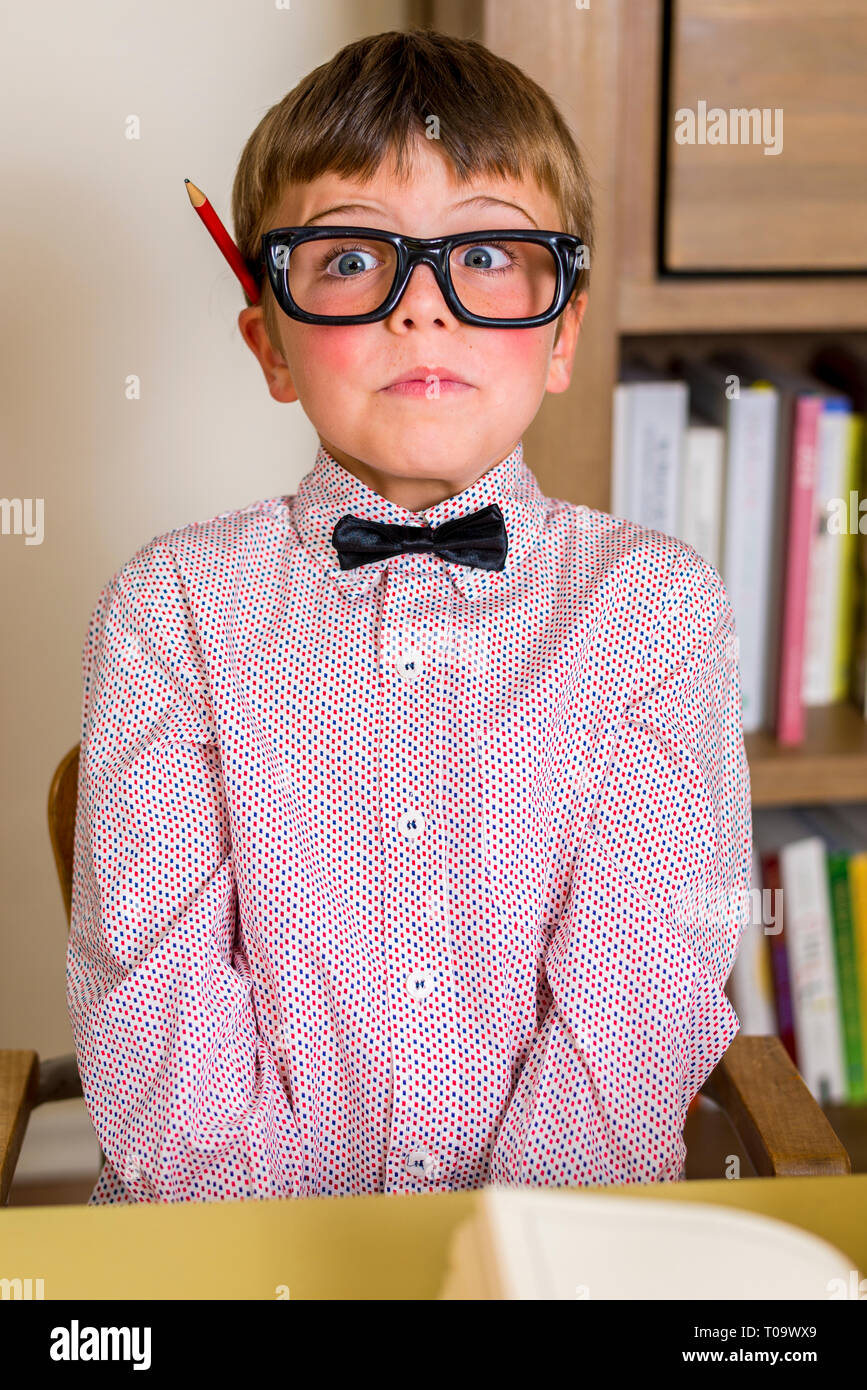 little nerdy boy with geeky goggles, making facial expressions. - Stock Image