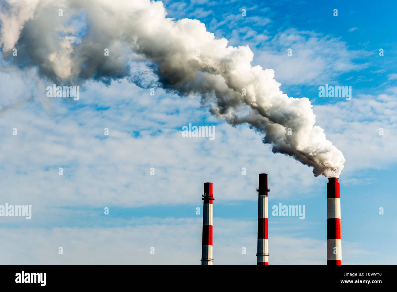 two chimneys of a power plant, one with heavy smoke - Stock Image
