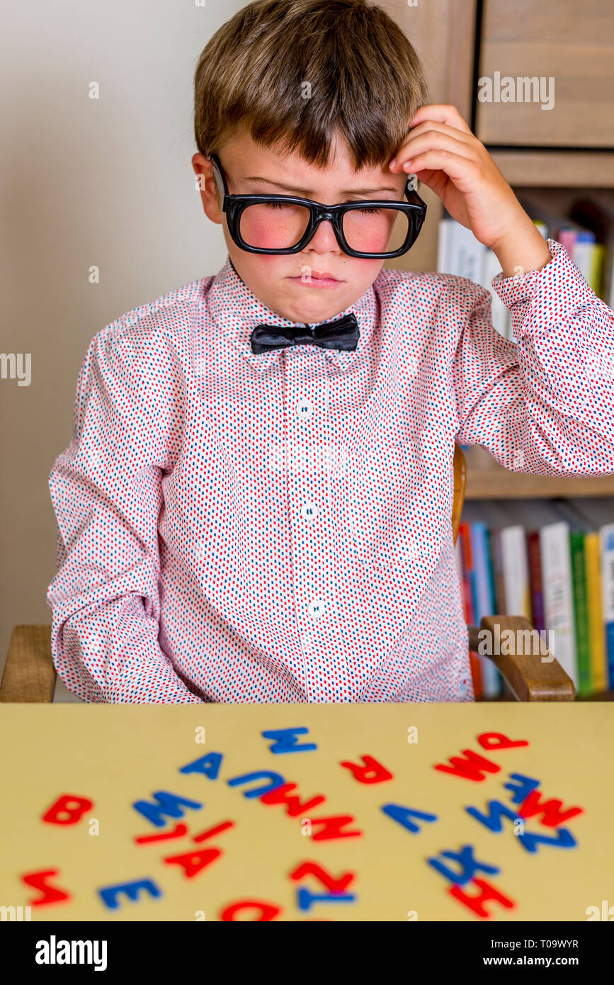 little nerdy boy with geeky goggles thinking real hard. - Stock Image