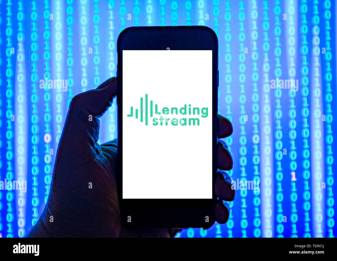 Person holding smart phone with  Lending Stream crowd funding logo displayed on the screen. - Stock Image
