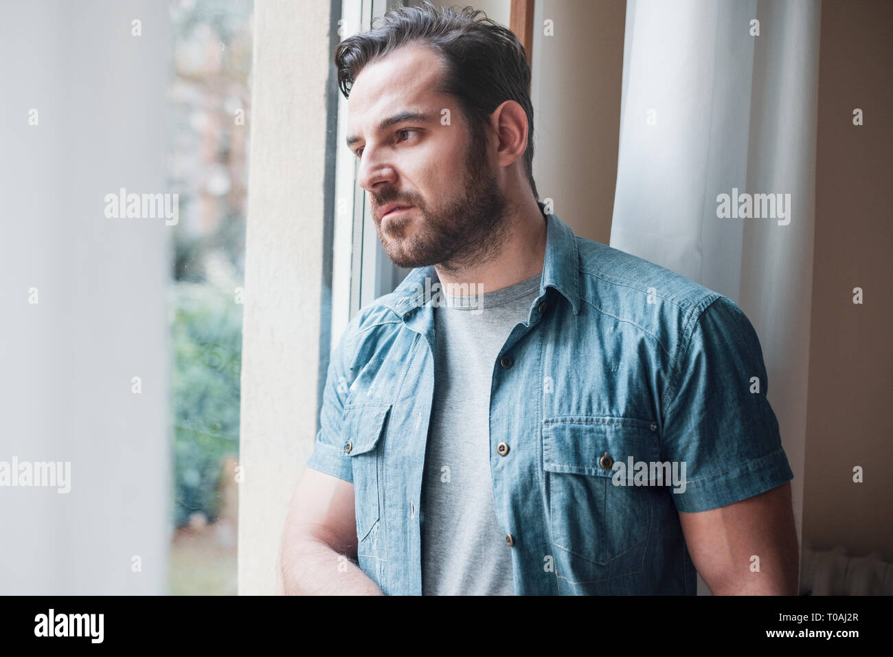 Man suffering and feeling alone at home - Stock Image