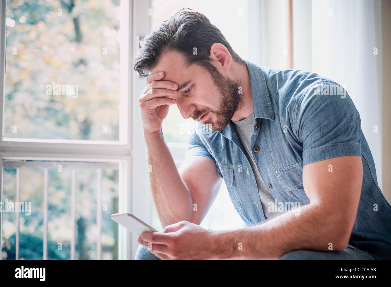 Sad man holding phone alone at home - Stock Image